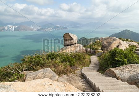 Scenic view of rocky landscape, stairs, ocean and Hong Kong Island from the Ling Kok Shan hill at the Lamma Island in Hong Kong, China.
