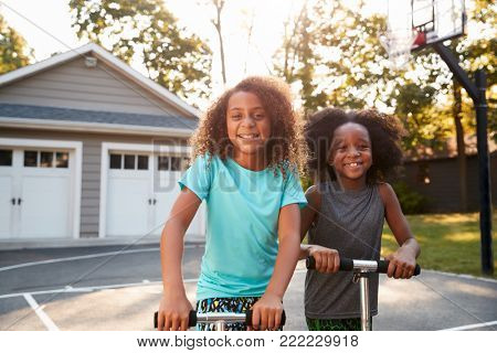 Brother And Sister Riding Scooters On Driveway At Home