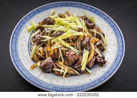 Chinese food. Stir fry beef with onion and leek on the porcelain plate. Black background.