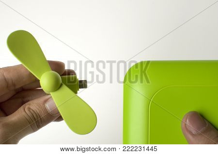 A man is inserting a green mini fan to a power bank against white background
