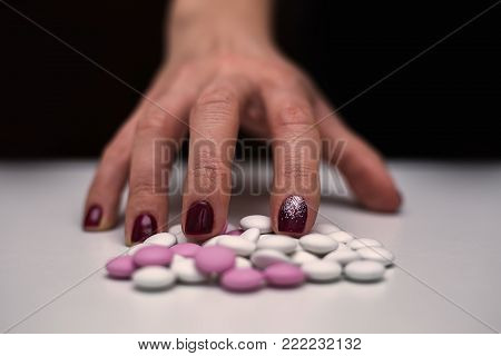 Closeup young woman hand with pills. Overdose and suicide concept.