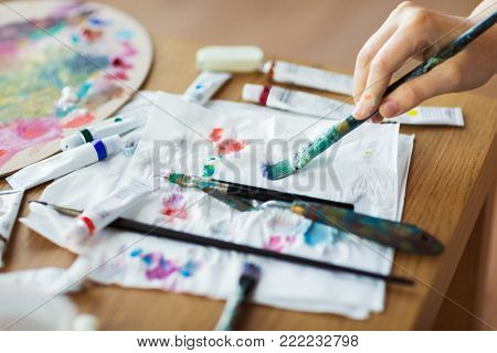 fine art, creativity and artistic tools concept - artist hand drying paintbrush with paper tissue