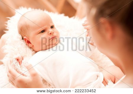 Funny baby lying on mother hands looking at each other close up. Motherhood. Good morning.