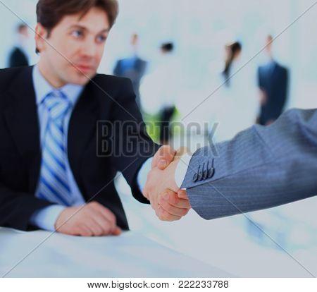 Close up of businessmen shaking hands.