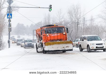 Snowplow is cleaning a street in the city