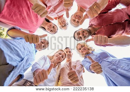 generation and people concept - happy family looking down standisg in circle and showing thumbs up