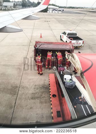 January 15, 2018, Khon Kaen Province, Thailand,  Airport staff of AirAsia are carrying luggage to the plane before departure from Khon Kaen International Airport to Don Mueang International Airport