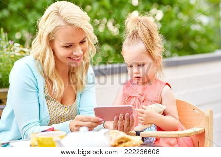 family, technology and people concept - happy smiling mother and daughter with smartphone at cafe or restaurant terrace