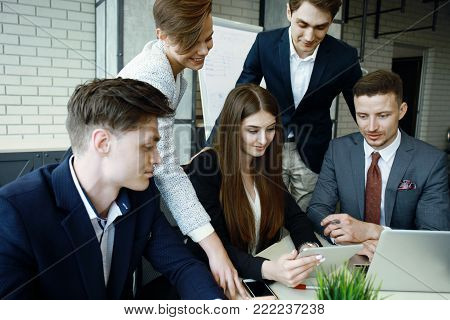 Brainstorm. Group of business people looking at the laptop together. One business woman looking at camera