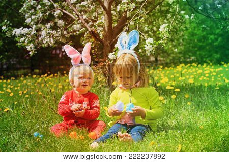 cute happy little girls on easter eggs hunt in spring nature