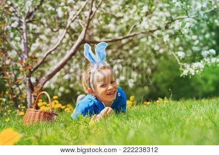 cute happy little boy on easter eggs hunt in spring nature