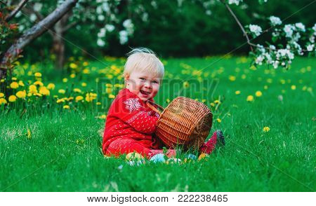 cute happy little girl on easter eggs hunt in spring nature