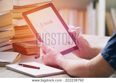 Man holding a modern ebook reader in hands on a table with piles of books iand bookshelf n the background