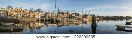 Blokzijl, The Netherlands - November 24, 2016: Panorama of the harbor with two flat bottoms (ships) of Blokzijl in the province of Overijssel. With old monumental houses and church.