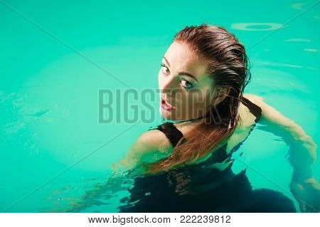 Sexy seductive woman wearing black dress in swimming pool water. Young attractive alluring girl floating.