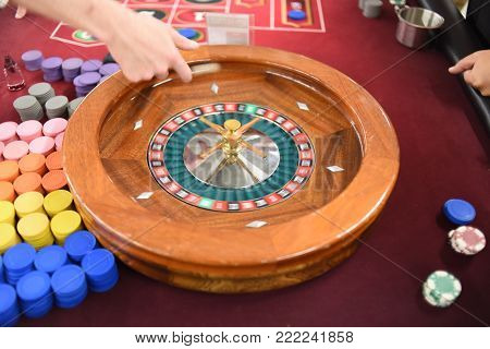 Casino dealer hand spinning a wooden roulette wheel on a red felt table with chips on the side for gambling