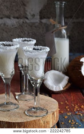 Coconut Milk In Bottle With Broken Coco On Wooden Background. Delicious Milk Cocktail. Copy Space