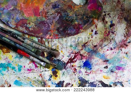 workplace painter palette with colors and brushes. Palette of colors, creative disorder, art.