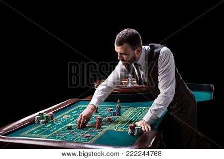 Croupier behind gambling table in a casino on a black background. Gambling. Casino. Roulette. Poker