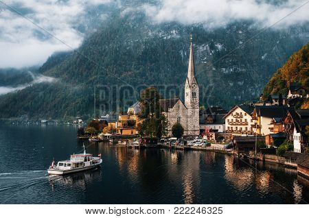 Electric small ferry arrives at the pier of Hallstatt town reflecting in Hallstattersee lake in the Austrian Alps in morning, Salzkammergut region, Austria