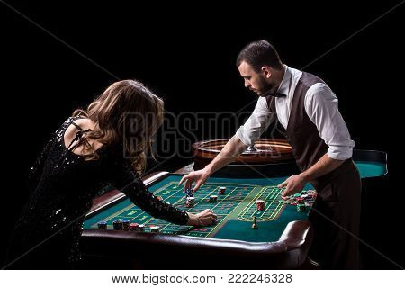 Croupier and woman player at a table in a casino. Picture of a classic casino roulette wheel. Gambling. Casino. Roulette. Poker