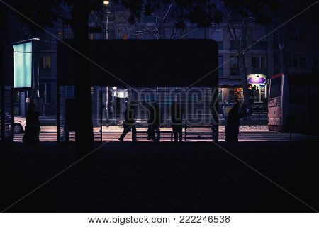 A night city scene, a bus stop with a couple of waiting passengers. The bus passed, winter on the street.