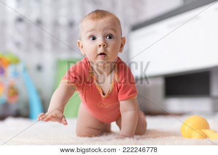 Funny baby boy crawling on the floor in nursery room
