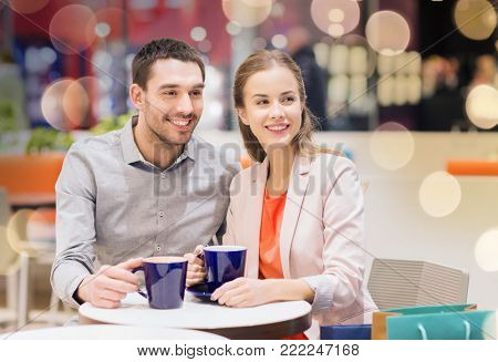 sale, shopping, consumerism, leisure and people concept - happy couple with shopping bags drinking coffee in mall