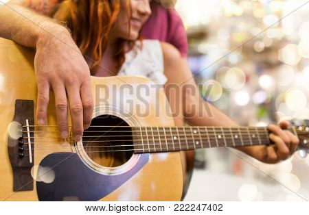 music, sale, people, musical instruments and entertainment concept - close up of happy couple of musicians playing guitar over lights background