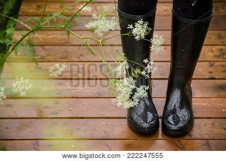 Closeup of woman's legs in black rubber boots on wet wooden surface. After rain, outdoors