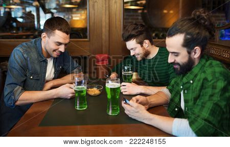 st patricks day, technology and leisure concept - happy male friends drinking green beer and messaging on smarphones at bar or pub