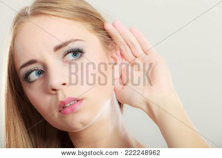 Closeup female hand to ear listening on gray. Gossip girl with palm behind ear spying. Young woman listening secret.