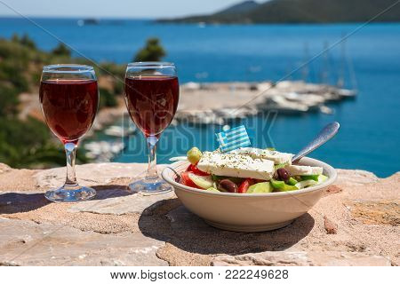 Two glasses of red wine and bowl of greek salad with greek flag on a stone terrace by the sea view, summer greek holidays concept. Horizontal. Daylight.
