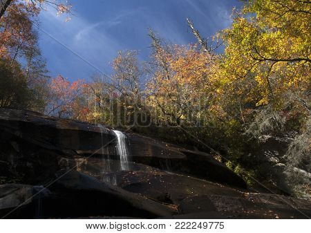 Wispy stream of water flowing over an almost dry waterfall in autumn in Pisgah Forest, North Carolina