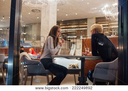 two young business people, freelancer working on same project meet for discussion and work at coworking hub or office cafe at night time, talk and discuss important topics at casual atmosphere