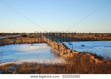 Stone wall crossing a frozen pond at the unique landscape The Great Alvar Plain on the swdish island Oland