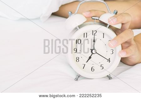 Closeup woman hand turn off alarm clock on white bed in the morning for wake up time concept