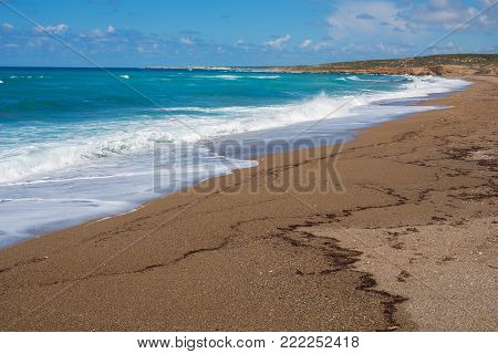 Shrouded boats on the seashore on a sunny day - a anticipation of adventure. Cyprus, the Akamas Peninsula.
