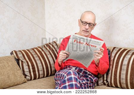 A man wearing glasses and pajamas is sitting on a couch at home, reading a newspaper reporting fake news