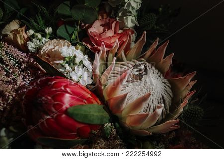 wedding rings on a bouquet of a bride in a flower of a protea