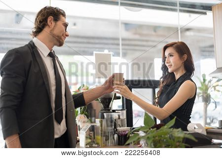 Attractive young beautiful caucasian barista in apron smiling to businessman costomer while giving coffee to him in coffee shop counter.Coffee Business owner Concept