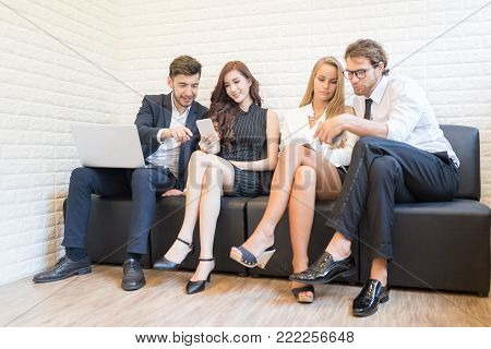 Happy Young Smart Confident Business People on Relaxing Break.Group of Business Persons with Age Variety Using Electronic Devices and Gadgets in the Modern Office. Inselective Focus.