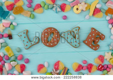 Word love in frame from candies. Composition from candies and cookies for Valentines Day. Love and romance concept.