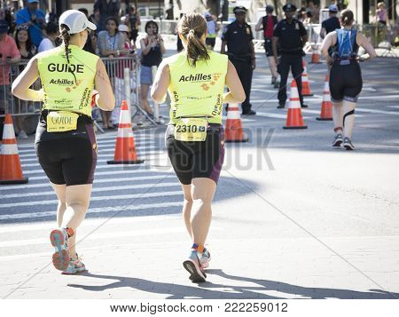 NEW YORK - JULY 16 2017: Achilles International athletes run on West 72nd St during the 10k portion of the Panasonic New York City Triathlon Race, the only International Distance triathlon in NYC.