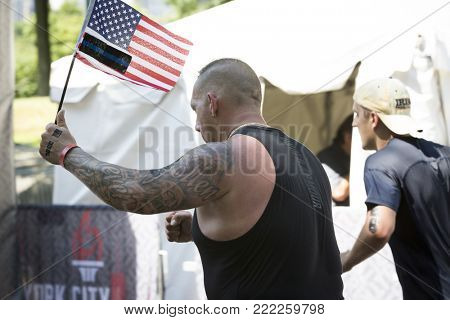 NEW YORK - JULY 16 2017: Athlete holding the American Flag crosses the finish line in Central Park of the Panasonic New York City Triathlon Race, the only International Distance triathlon in NYC.