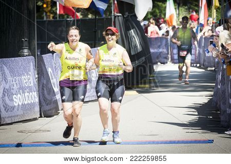 NEW YORK - JUL 16 2017: Achilles International athletes approach the finish line in Central Park of the Panasonic New York City Triathlon Race, the only International Distance triathlon in NYC.