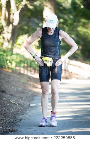 NEW YORK - JUL 16 2017: Athlete stops to rest in Riverside Park during the NYC Triathlon Race in Central Park. The run is 10k and the race is the only International Distance triathlon in NYC.