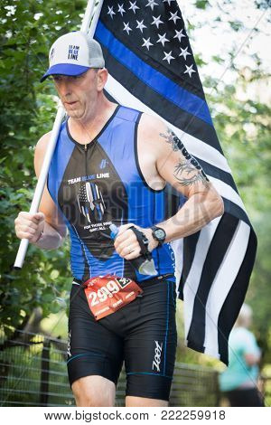 NEW YORK - JUL 16 2017: Athlete runs through Riverside Park carrying a flag during the 10k portion of the Panasonic New York City Triathlon Race, the only International Distance triathlon in NYC.
