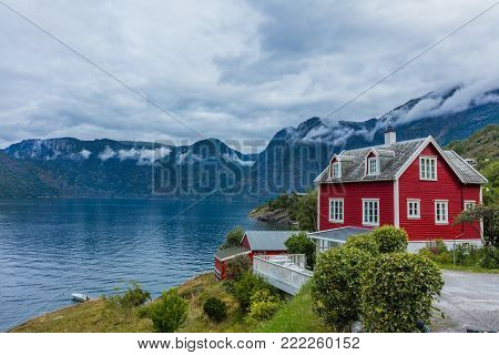 Typical red wooden cottage near the fjord. Stone snowy mountains, Norway.