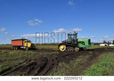 OSAGE, MINNESOTA, Sept 26, 2017: The 9620 T tractor pulling a truck stuck in mud is a product of John Deere Co, an American corporation that manufactures agricultural, construction, forestry equipment, machinery, and diesel engines,